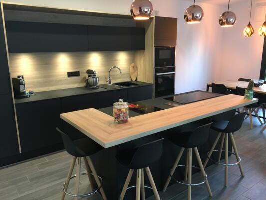 Cuisine design noire et bois ouverte avec ilôt