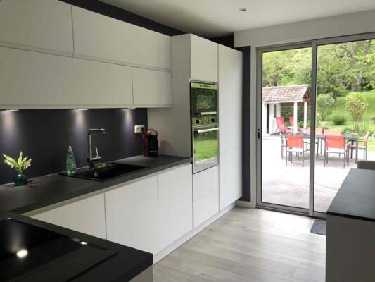 Cuisine design noire et blanche en angle avec mur d'armoire