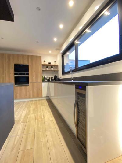 Cuisine moderne blanche et bois avec mur d'armoire