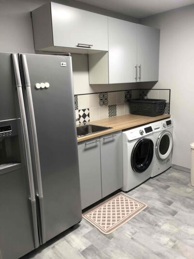 Cuisine moderne blanche et grise avec réfrigérateur