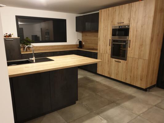 Cuisine moderne noire et bois en angle avec mur d'armoire