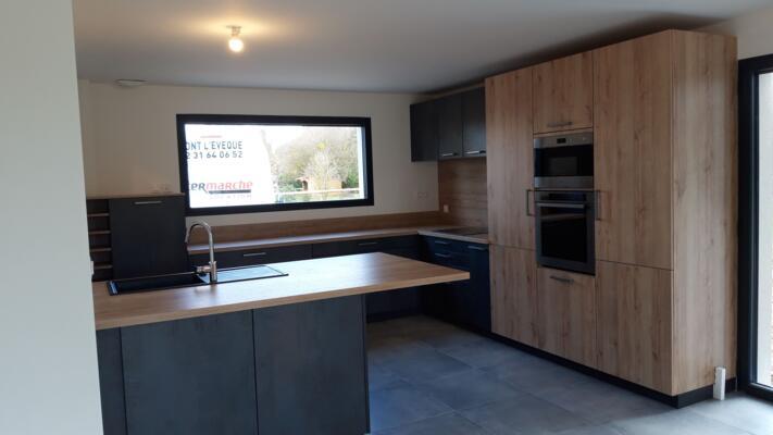 Cuisine moderne noire et bois ouverte avec mur d'armoire