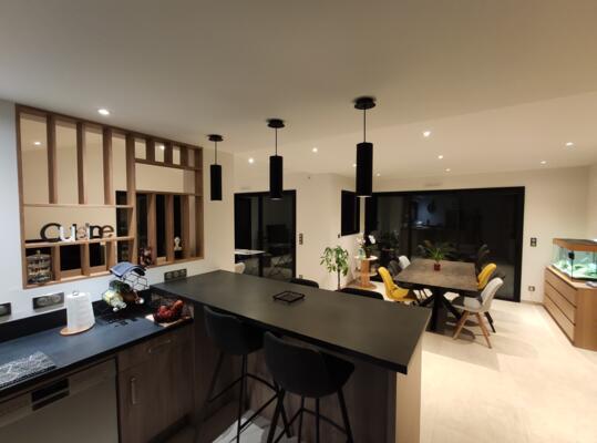 Cuisine moderne noire et bois ouverte avec verrière