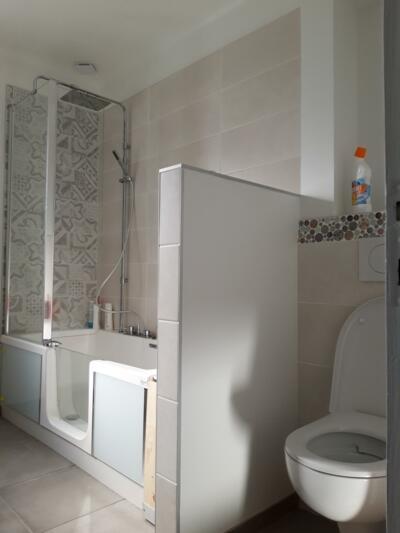 Salle de bain avec baignoire à porte