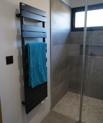 Salle d'eau avec douche à l'italienne grise et sèche serviette noir